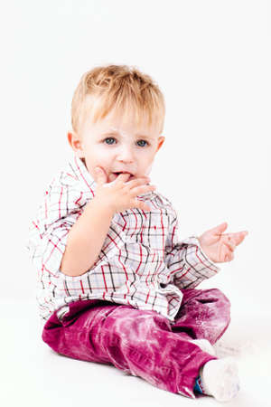 smeared: Little messy with flour boy on white background. Close-up of small baker eating his fingers. Homemade cuisine, mother helper, happy family concept