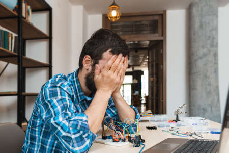 Engineer closed his face in despair, free space. Side view on electrician sitting near his non working electronic construction. Failed connection, broken details, unsuccessful experiment Stock Photo
