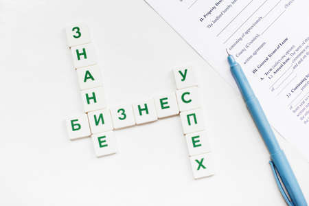free space: Russian  words on business concept with pen and contract paper. Featured words are: Knowledge, Business, Success. Isolated with free space