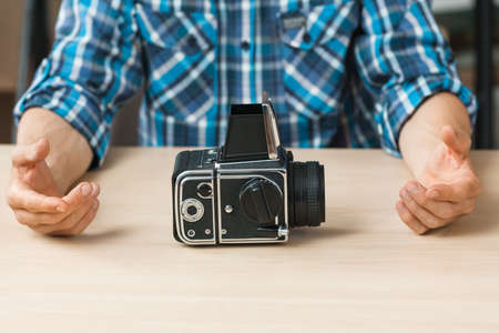 free space: Professional retro photo camera presentation. Unrecognizable photographer talking about old fashioned photographing equipment, free space for text or advertisement