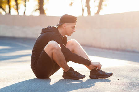 Young sporty man sitting on ground at stadium at sunset. Sportsman preparing for workout before competition, tie shoelaces, blurred photo. Healthy lifestyle, sport, hobby concept
