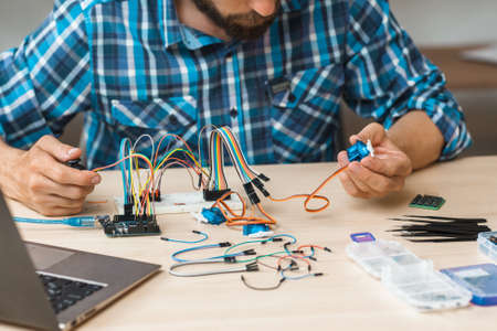 Engineer checks connection between components on his construction. Failure search in creation. Modern technologies, electronics, diy product engineering