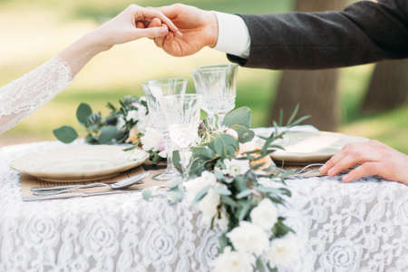 結婚式: 上記の手を繋いでいるカップルは、テーブルを提供しています。新郎は彼の花嫁に立ち上がることを助けます。愛、エチケット、ケアの概念 写真素材