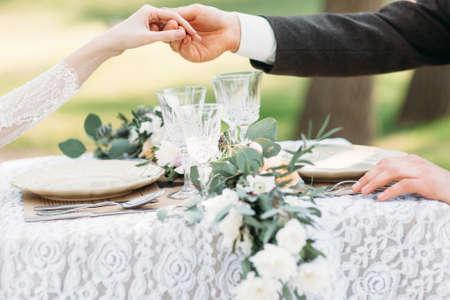결혼식: 봉사 테이블 위에 손을 잡고 몇입니다. 신랑은 일어 서서 그의 신부를 도와드립니다. 사랑, 예절, 관리 개념