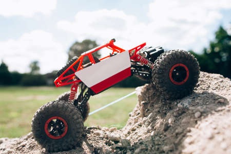Side view on rc crawler rising on rock hill. Toy suv climbing on mountain road, profile. Extreme sport, hobby, entertainment concept Stock Photo