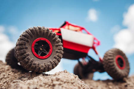 Rc crawler outside, view from below. Red and white toy suv on rocky terrain, blue sky on background, free space Imagens