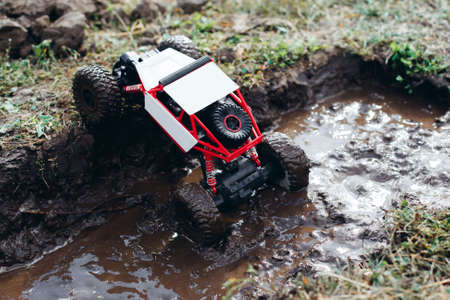 Toy rc car rising from puddle of mud. Small crawler roading on bad conditioned countryside. Bad weather, dirt racing competition of controlled toys outdoor, hero of the day, survival concept