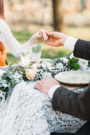 Groom holding his bride hand close-up. Man ask his lovely fiancee for dance while sitting at dining table. Wedding, tradition, love concept Banque d'images