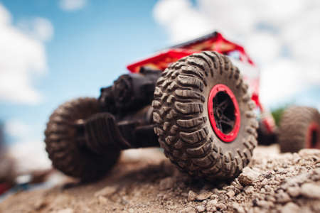 Red crawler wheels outside close-up. Rc car standing on rock, blue sky with clouds on background