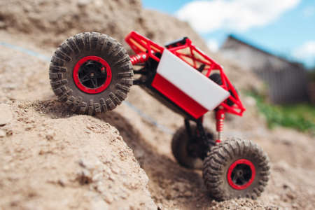 Rc crawler overcoming mountain rise, close-up. Country land adventure, toy suv riding on rock landscape. Entertainment, hobby, rally concept