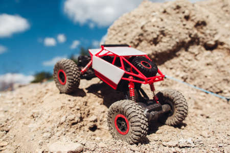 Rc car riding on rock land, close-up. Toy suv driving on offroad trace. Toy, competition, entertainment , expedition, explorer concept