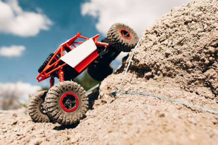 Suv overcoming rock rise, close-up. Rc crawler riding through mountain landscape. Truck overpass offroad rally trace.