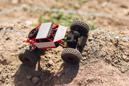 Toy crawler riding off road rally, copy space. Side view on rc suv racing country landscape. Buggy, adult hobby, entertainment concept