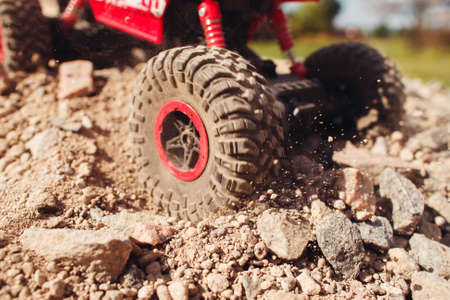 skid: Close-up of wheel slipping in rock trace. Toy truck skid on rocky surface, hard road condition, traffic trouble concept