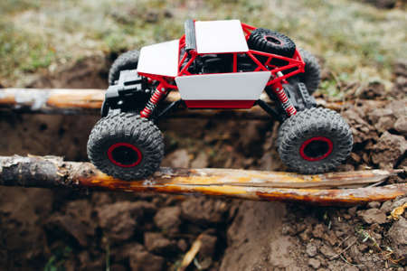 Rc car roading on wooden beams above hollow. Toy suv riding on log handmade bridge over yawner with mud. The competition of radio-controlled toys Stock Photo