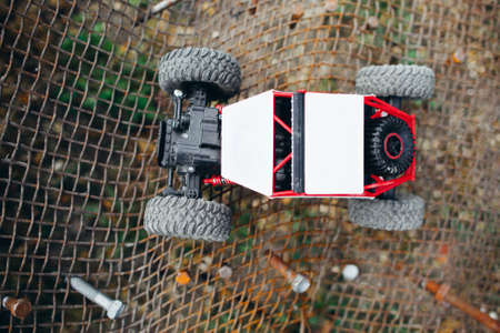 Rc truck on metal lattice, top view. Toy crawler riding on grille, suv driving facilities testing, free space