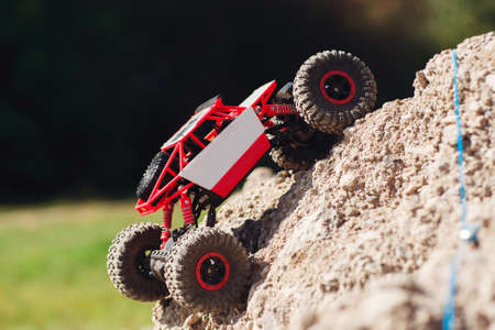 Side view on crawler rising on rock hill. Small buggy car overcoming mountain rough rock. Going to win, leisure, competition, extreme concept