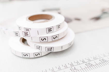 garment industry: Several size tag tapes on white background. Close-up of clothes proportions rolls. Professional tailor equipment, important supply for cloth making, garment industry concept