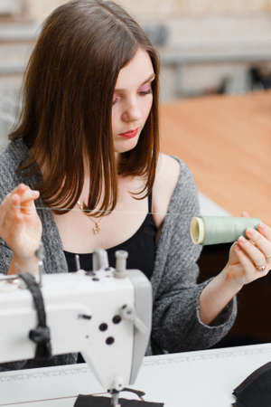 garment industry: Seamstress preparing for work at sewing machine. Female tailor unwinding thread at her workplace. Tailoring process, garment industry, business concept Stock Photo