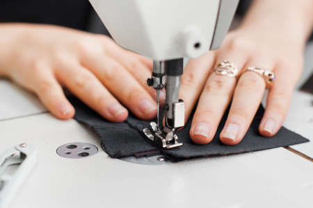 garment industry: Woman hands with fabric at sewing machine. Seamstress working behind her equipment. Tailoring process, designer workshop, garment industry concept