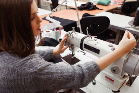 garment industry: Seamstress tuning sewing machine for work. Young female tailor fixing stuck thread on her work equipment. Tailoring process, designer workplace, garment industry concept Stock Photo