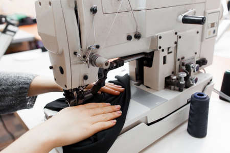 Woman stitching dark fabric on sewing machine. Close-up of seamstress hands making clothes on professional equipment. Garment industry, designer atelier, tailoring process concept Archivio Fotografico