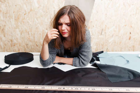 garment industry: Overworked designer crying above fabric. Stressed tailor preparing material for sewing clothes. Garment industry, tailoring process, pattern cutting concept