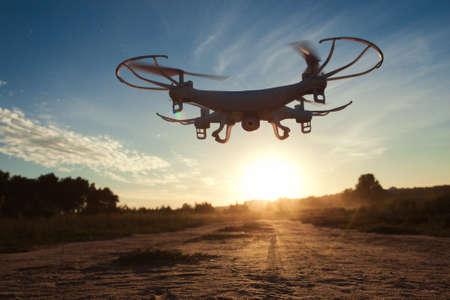 Hommel die openlucht in avond, zonsondergangachtergrond vliegen. Quadrocopter video opnemen van omgeving. Werk, innovatie, moderne technologieën, vrijetijdsconcept