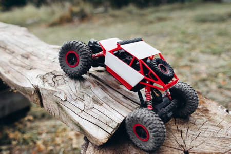 Rc car overcoming wooden log, free space. Small crawler rising beam. Toy suv roading off road landscape.