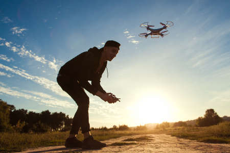 Piloting drone in field, sunset flare, free space. Young man running quadrocopter outdoor on blue sky background. Leisure, entertainment, modern technologies concept