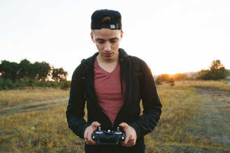 free space: Serious man with remote controller portrait, free space. Young guy attentively piloting drone. Real time record, leisure, work, technology, electronics concept Stock Photo