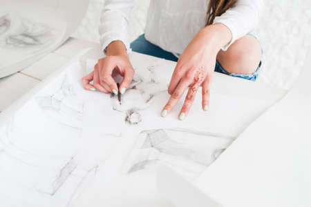 unrecognizable: Artist hands drawing sketch on whatman or white paper. Female painter painting in studio. Stylish woman with mehendi oh hand working in workshop. Art, talent, craft, hobby, creativity concept