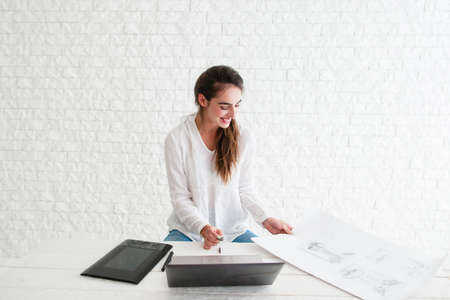 free space: Smiling woman at workplace, free space. Glad designer retouching sketch on laptop. Happy artist satisfied of her work. Art, talent, craft, hobby, work, creativity concept Stock Photo