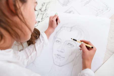 Kunstenaar tekening potlood portret close-up. Vrouwenschilder die foto van vrouw op grote watman creëert. Kunst, talent, ambacht, hobby, beroepskoncept