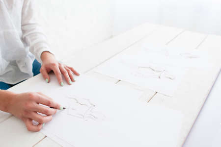art and craft: Hands of young designer creating new collection. Creative artist drawing female silhouettes in dresses on white paper. Art, craft, talent, inspiration, fashion concept Stock Photo