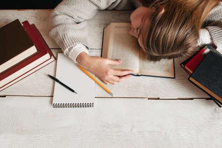 cansancio: Muchacha del estudiante que duerme en el escritorio con libros aplanada. Vista superior de joven mujer cansada durmiendo en su libro de texto. El cansancio, el agotamiento, la educación, la preparación para los exámenes concepto