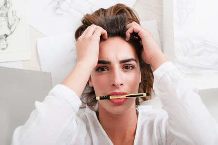 bad news: Shocked woman looking at camera with pencil in mouth. Top view on lying artist heard bad news while drawing. Stress, depression, art, workshop , exam concept
