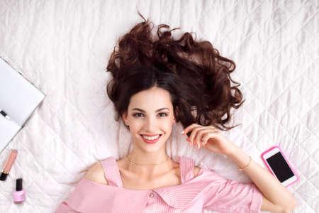 Belle femme couchée sur le dessus de lit vue. brune heureuse en rose avec des cheveux parfaite santé souriant à la caméra. Beauté, la joie, la santé, le concept de la mode