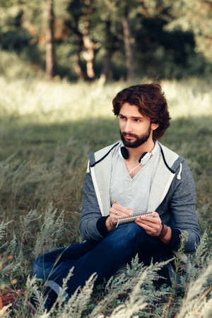 Author writing poem at nature, free space. attractive man sitting with notebook, came for inspiration to meadow. Relax, idea, thinking concept Stock Photo