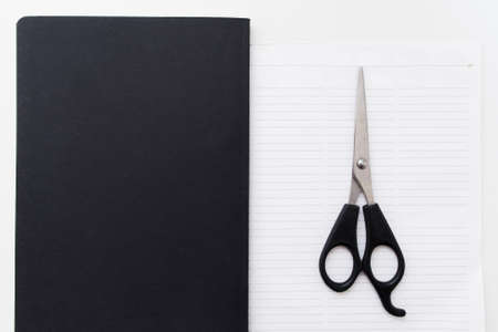 délivrance: Scissors on blank notepad flat lay free space. Top view on open blank notebook with cutter on first page. Business, stationery, modern life, contrast, brend book, deliverance concept concept Banque d'images