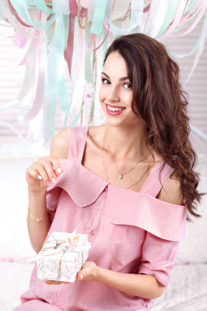 Pleased woman holding gift box in hand. Beautiful woman in pink dress with present pack smiling at camera. Holiday, surprise, joy, happiness, Birthday, pleause concept