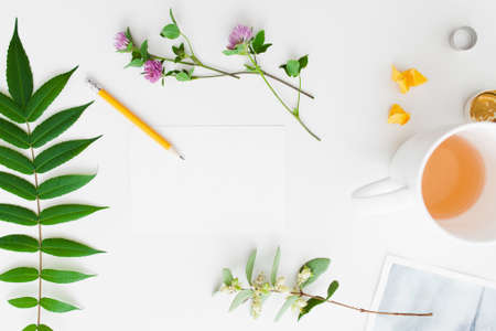 artisan: Accessories for handmade craft flat lay. Top view on artisan workplace with green leaves with flowers and cup of tea, free space. Art, hobby, craft concept Stock Photo