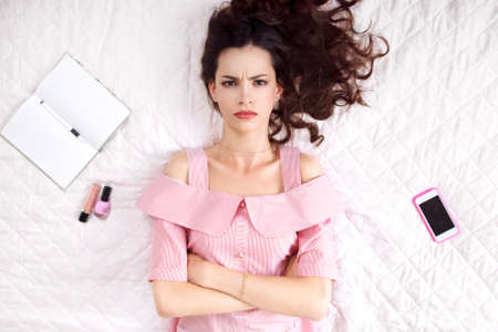 Pouted woman lying with crossed hands on bed top view. Resentful brunette in pink looking at camera, ready to cry. Offence, caprice, feeling concept