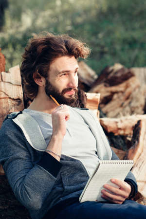 Thinking guy with notebook on pile of wood. Young man speculating about building, repair, to do list, shopping list, leaning on firewood bunch. Stock Photo
