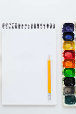 aquarelle painting art: Blank notebook with pencil and watercolor palette mockup, flat lay. Top view on empty sketchbook with colorful aquarelle variety. Art, workshop, painting, craft, creativity concept