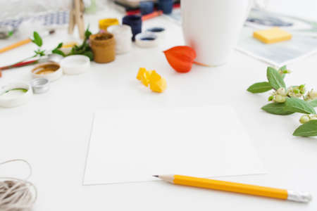 Messy artist workplace with tools, free space. White table with blank card, pencil, cup of tea and drawing instruments. Art, creativity, inspiration, imagination concept
