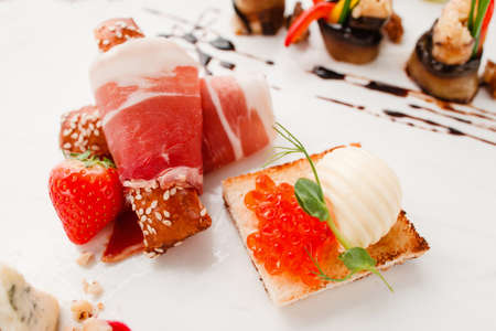 expensive food: Bacon rolls with caviar toasts close-up. Tasty appetizers on white plate, delicatessen mix. Luxury lifestyle, expensive food, restaurant menu, gourmet concept