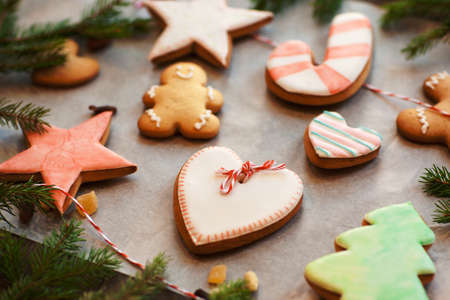Colorful gingerbread cookies on cooking parchment. Various sweet snacks prepared for holiday and decorated with love. Homemade pastry, Valentine hearts concept Stock Photo