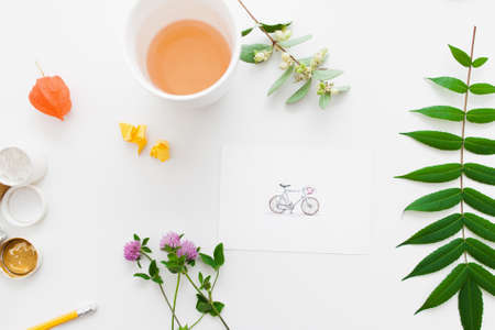 artisan: Cup of tea on artisan workplace with plants flat lay. Top view on table with picture of cute bicycle, green leaves and flowers and hot drink. Art, inspiration, craft, leisure concept