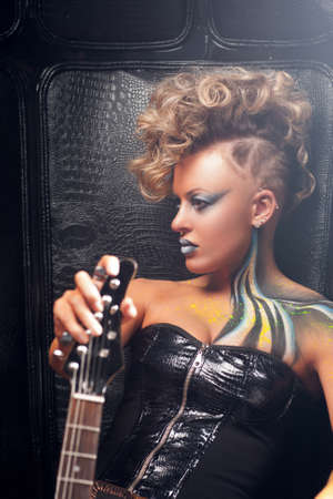 rocker girl: Beautiful woman punk with bass guitar profile. Attractive rocker girl in leather cloth, with bright body art and hairstyle, posing with her musical instrument. Subculture, lifestyle, fashion concept